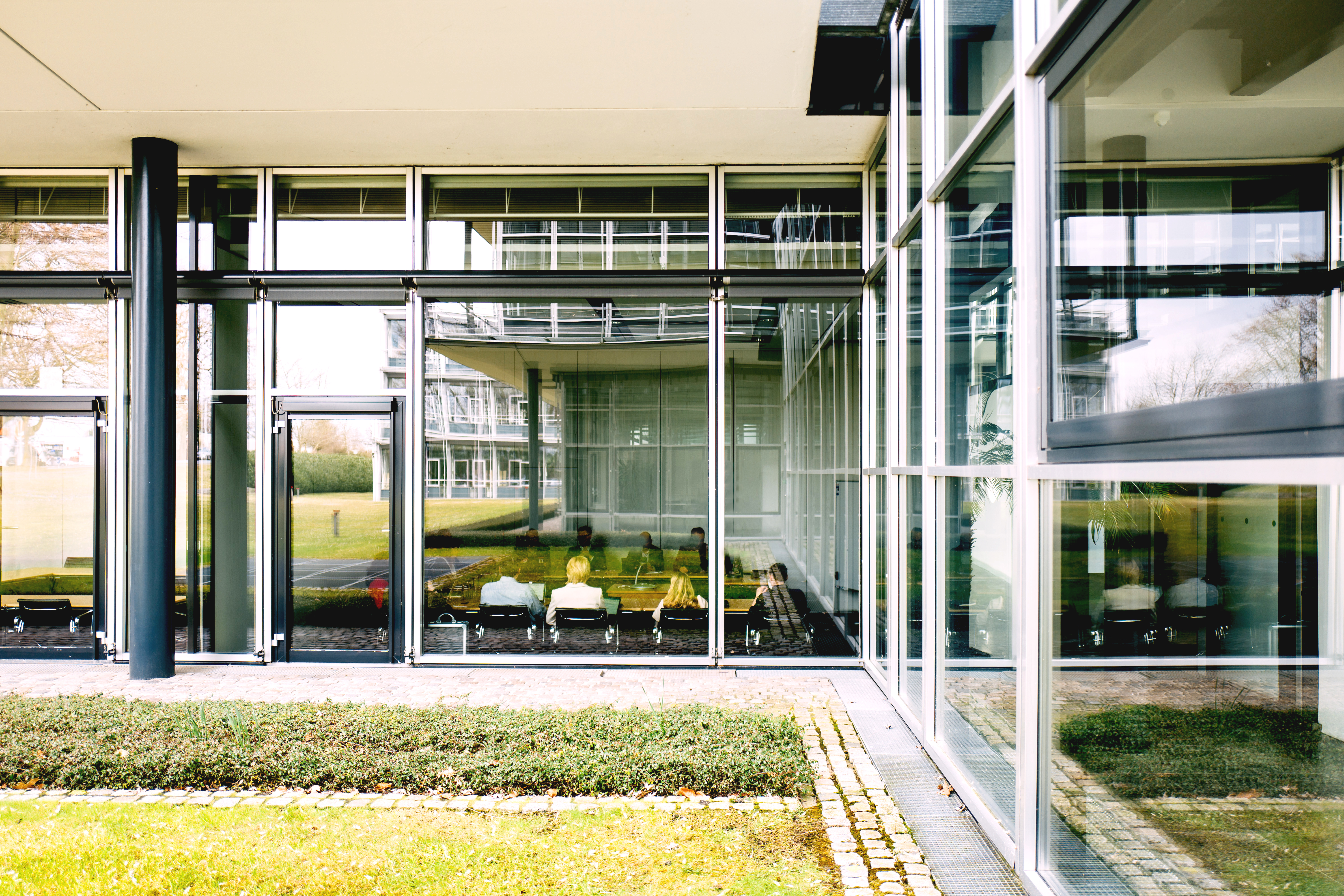 View from the outside onto a glass inner corner of the Bertelsmann Stiftung building. Inside, people are sitting at a conference table.