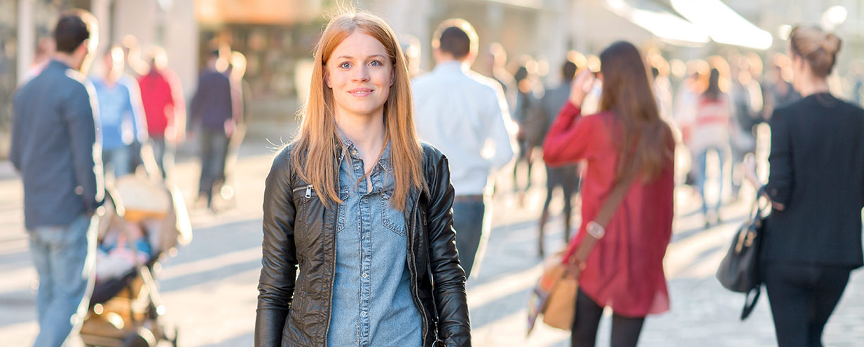 A young woman with longer red hair stands in a busy pedestrian zone. She looks expectantly into the camera.
