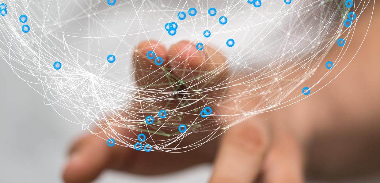 Une personne touche un graphique informatique avec deux doigts qui représente une balle ou un globe composé de lignes et de points connectés.  Le graphique est représentatif d'un réseau.
