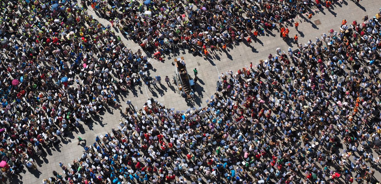 A huge crowd has assembled around a tall lectern on a town square. The crowd is shown from bird's eye view.