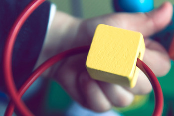 Ein Kind spielt in einer Kindertagesstätte an einem Drahtperlenspielzeug. Vom Kind ist nur eine Hand zu sehen.