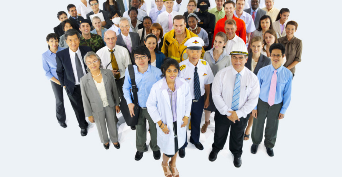 A group of people in working dress, including a doctor, a pilot, a firefighter, business people and construction engineers. They are standing closely together in a large group and smile into the camera.