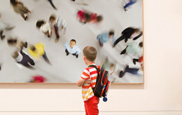 Young boy looking at picture in gallery from where a man is looking back at him.