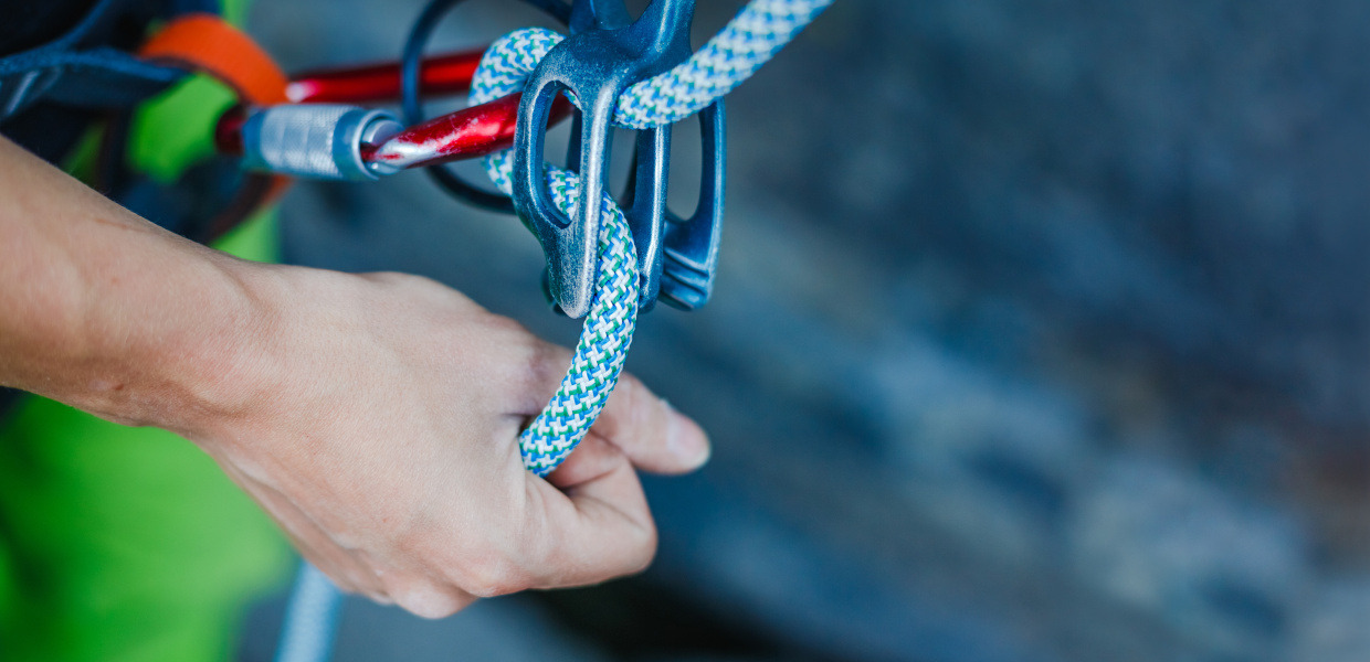 A climber wears safety equipment and holds the safety rope by hand.