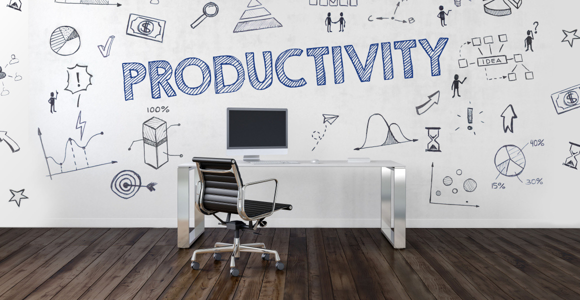 In a room, the word Productivity appears like a graphic. In front of the wall stands a brown office chair at a desk.