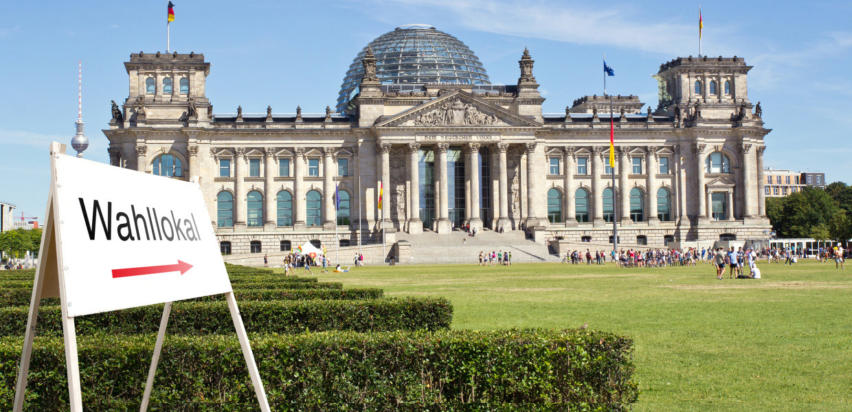 In front of the Reichstag building in Berlin there is a sign pointing to a polling station.