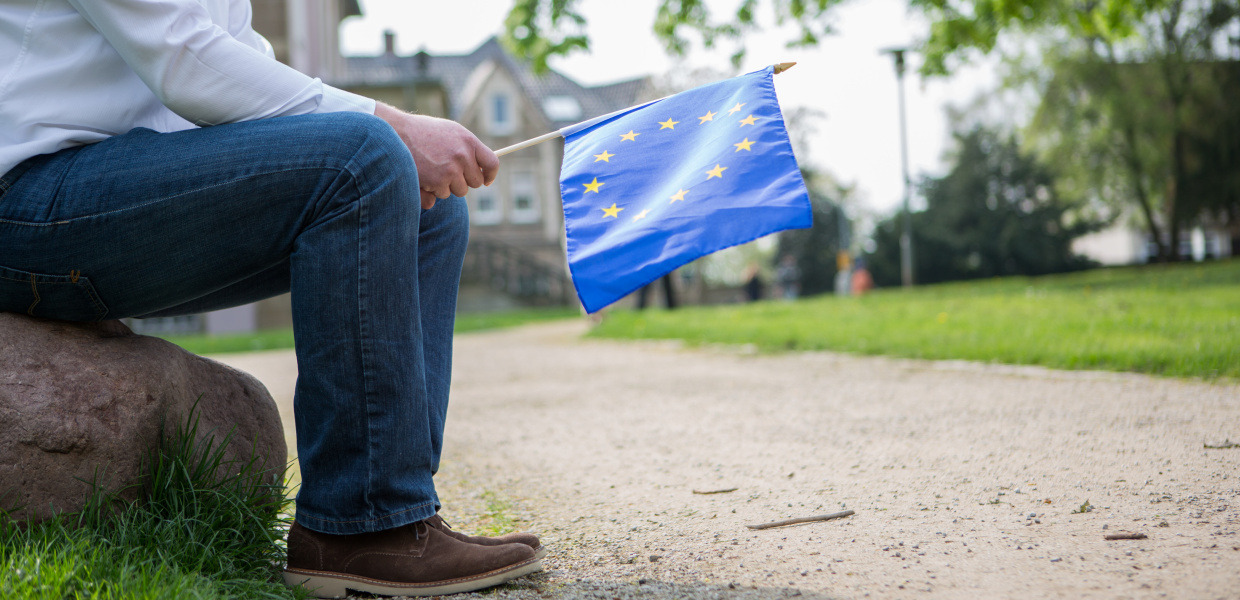 A man sitting on a stone and holding the flag of the EU.