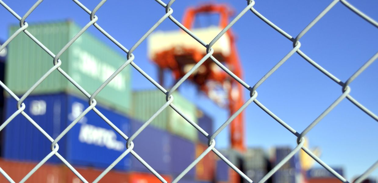 A chain-link fence blocks the entrance to a harbor. A container crane and a few containers are visible in the background.