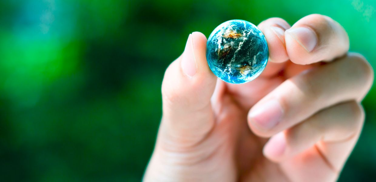 A person is holding the globe which has shrunk to the size of a marble between thumb and index finger.