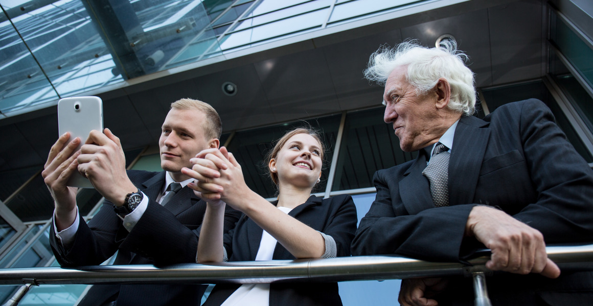 Three businessmen, a young woman, a young man and an older man talking on the observation balcony of a corporate building.