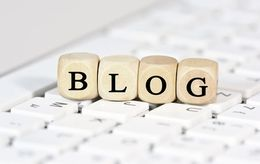"""Eine Holzkette mit Buchstaben darauf liegt auf einer Tastatur. Die Buchstaben ergeben das Wort """"Blog"""""""