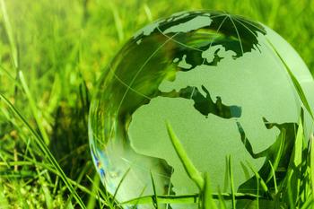 Eine Weltkugel aus Glas auf einer grünen Wiese.