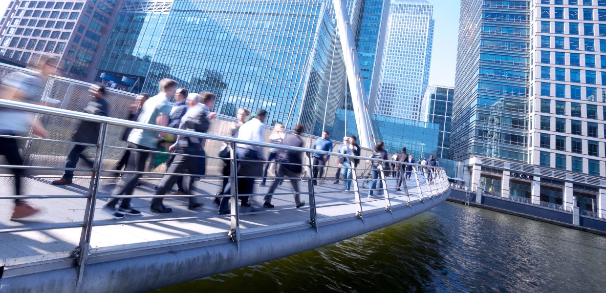 Several businesspeople walk across a bridge in the City of London, London's financial district.