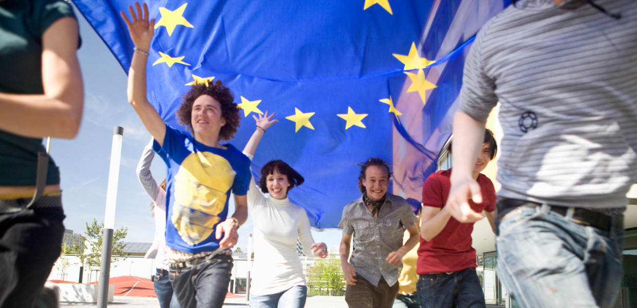 Group of young people running with an EU flag in Munich, Bavaria, Germany