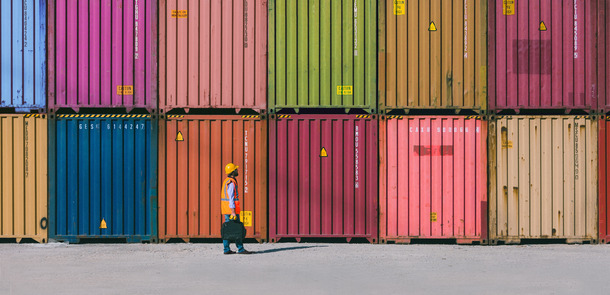 Engineer man with yellow crash helmet and worker west checking cargo freights in front of colorful cargo container stacks in shipping port.(© Getty Images/iStockphoto.com/serts)