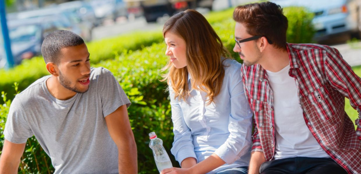 Three young people sit on a park bench and discuss.