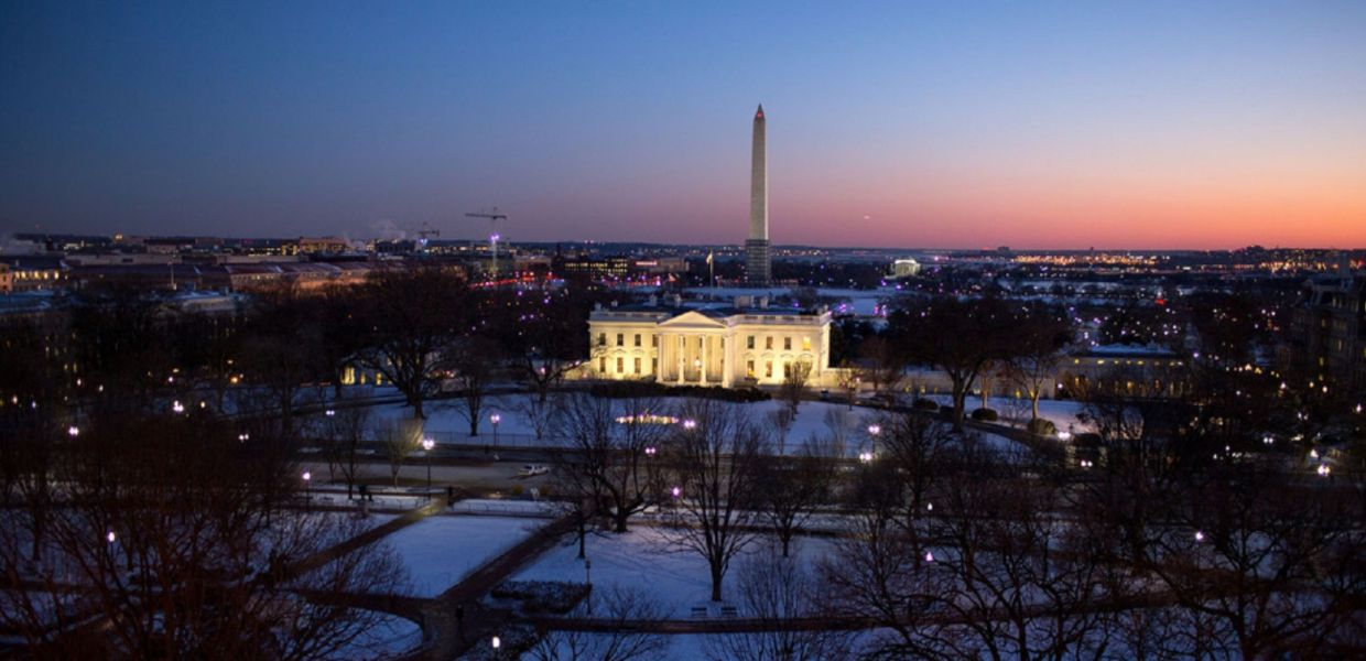 The illuminated White House in Washington, DC in dusk on a snowy winter evening. In the background one can see the obelisk of the Washington Monument.