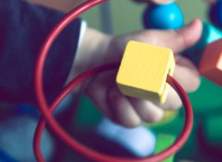 Kleines Kind spielt auf dem Boden mit einem Spielzeug. Dabei ist nur der Arm und das Spielzeug auf dem Bode zu sehen