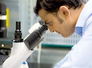 bestellt am 10.09.2014 für den Relaunch Webseite, erweiterte Lizenz incl. Mehrplatzlizenz; Closeup portrait, young scientist looking into microscope. Isolated lab background. Research and development.(© nandyphotos / Fotolia.com)