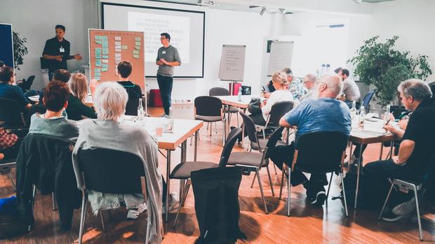 Open-Data-Workshop in Münster. Etwas 25 Personen sitzen in einem Raum. 2 Moderaoren stehen vorne an einer Metaplanwand.