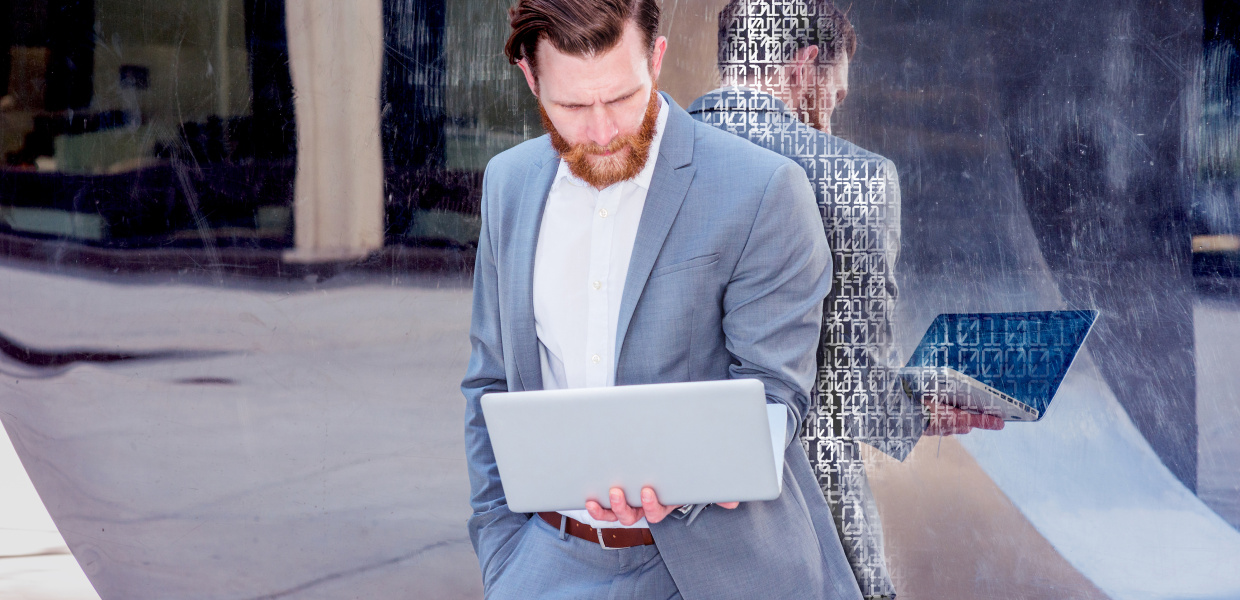 Keyvisual: Ethik der Algorithmen; bearbeitet/Retusche mit 0 und 1; American Businessman with beard, mustache works in New York. Young man wearing cadet blue suit, stands against metal mirror wall, looks down, reads on laptop computer. Filtered look with purple tint.; Shutterstock ID 520256158; Purchase Order: Ethik der Algorithmen; Job: 103-63133-131; Client/Licensee: Bertelsmann Stiftung; Other: ST-IFT  21.11.2017