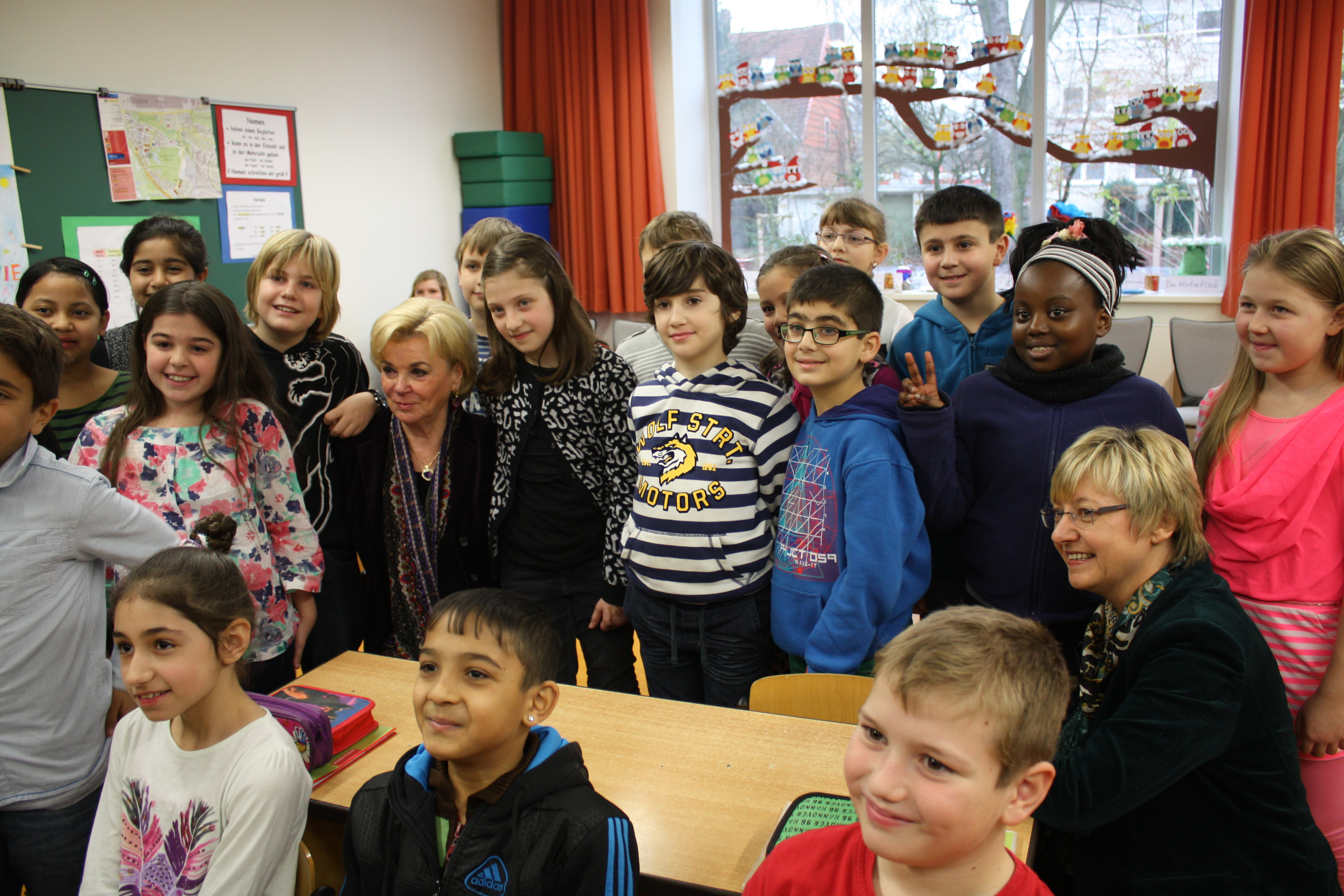 Liz Mohn surrounded by many students in a classroom