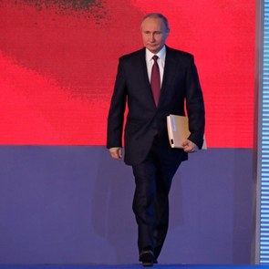 Vladimir Putin enters the stage for his Presidential Address to the Federal Assembly. In the background of the stage, one can see a projection of the Russian flag.