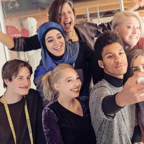 A group of non-Muslim and Muslim young people take a selfie in an office, smiling for the camera of the smartphone.