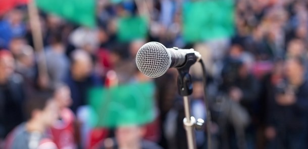 A microphone can be seen in front of a crowd which is holding up green placards.