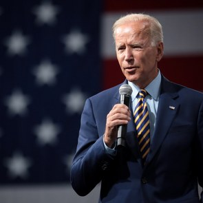 President-elect Joe Biden is giving a campaign speech in 2019 in Iowa. Behind him there is a giant US flag hanging on the wall.