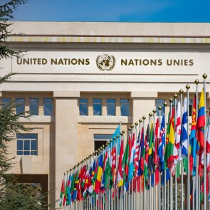 The entrance of the United Nations Office at Geneva with the flags of all nations in front of it.