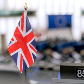 In the European Parliament in Strasbourg, a small British flag is standing on the desk of a member of Parliament. The parliament speaker's podium and the large EU flag above it can be seen in the background.