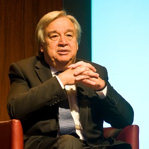 António Guterres speaks on the podium of the Vision Europe Summit while sitting in an armchair. Next to him one can see the Vision Europe Summit logo displayed on a large video screen.