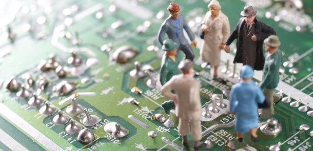 A group of elder people, represented by small figurines, is standing on the printed circuit board of a computer and talking to each other.