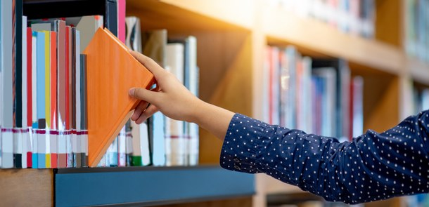 Male right hand choosing and picking orange book in public library