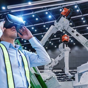 Engineers are using Virtual reality with VR glasses check and control automation robot arms machine in intelligent factory industrial on monitoring system software.
